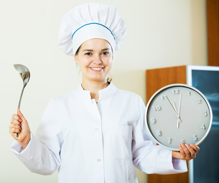 ready to cook food: Smiling woman in cook uniform waiting food to be ready with clock in hands