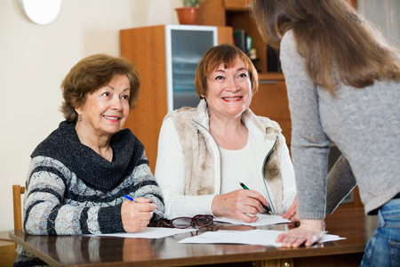 75s: Elderly cute positive women making will at public notary office and smiling Stock Photo