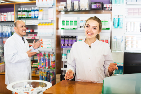 farmacy: Portrait of professional pharmacist and assistant working at farmacy reception Stock Photo