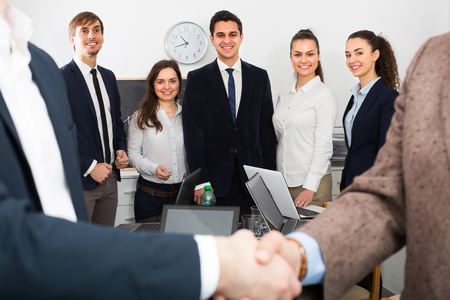 co operation: Two managers shaking hands at business meeting in office Stock Photo