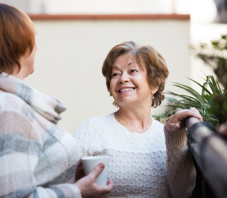 pullovers: Portrait of senior women in pullovers having cup of tea on terrace Stock Photo