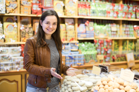 candy store: Portrait of happy young brunette shopping in candy store Stock Photo