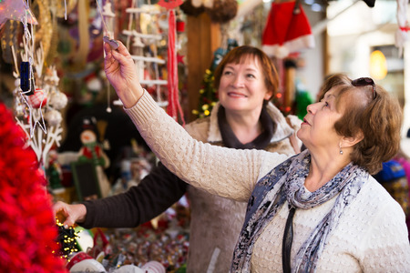70 75: Portrait of two senior women choosing decorations at counter of Christmas market Stock Photo