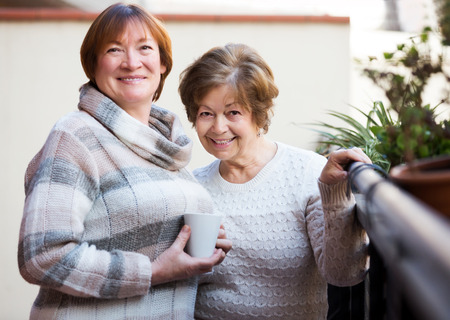 pullovers: Senior smiling women in pullovers having cup of tea on terrace