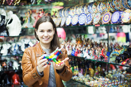 Young happy brunette choosing souvenir for memory