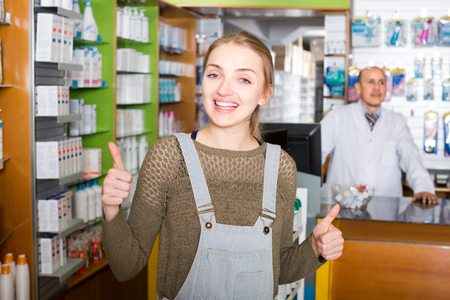 farmacy: Experienced medicine pharmacist counseling female customer in modern farmacy