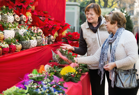 60 65 years: Happy smiling elderly women selecting floral compositions at Christmas market