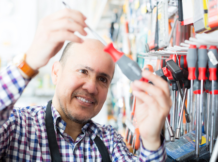 tooling: Portrait of positive mature seller offering working tooling in household store Stock Photo
