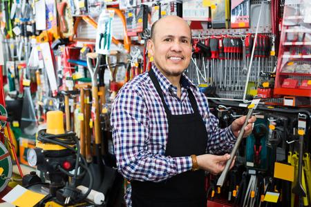 empleada domestica: vendedor maduro que presenta cerca de compresor eléctrico en la tienda del hogar