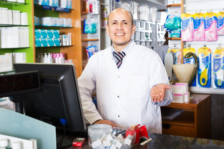 farmacy: Portrait of positive male pharmacist working in modern farmacy and smiling