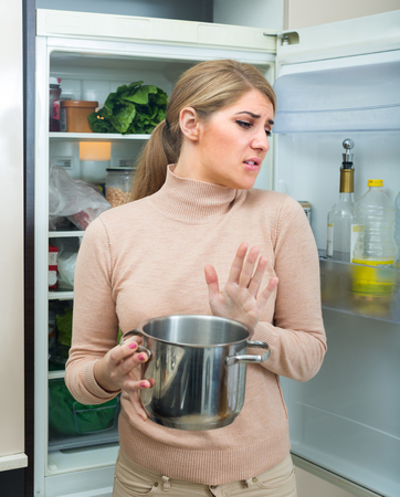 foul: Upset young housewife holding pot with foul meal near fridge