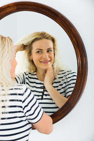 wellness sleepy: Portrait of long haired blondie checking her skin in mirror