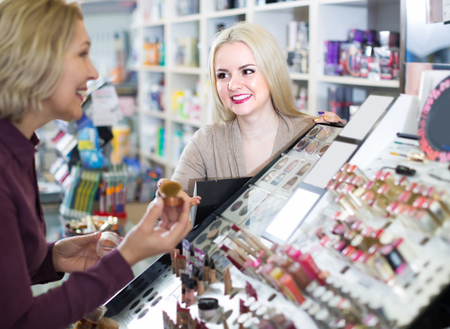 Friendly female seller near display with cosmetics in beauty store