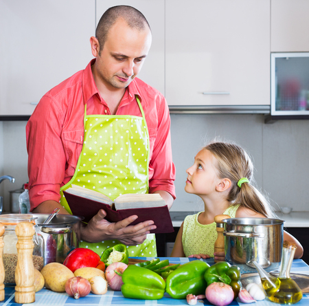 family meal: Portrait of positive dad and little daughter cooking in kitchen at home