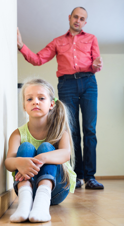 lecturing: Father lecturing offended little daughter in home interior