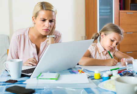 Tired young woman working online at home with little daughter nearby