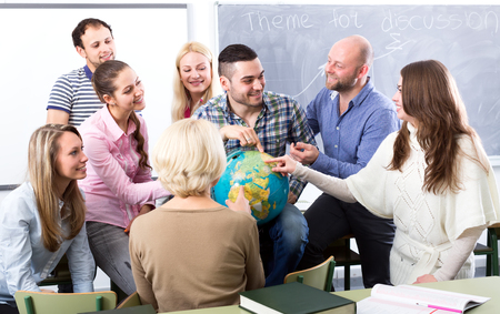 highschool students: Highschool students having fun with a globe at geography class during a break in a classroom Stock Photo