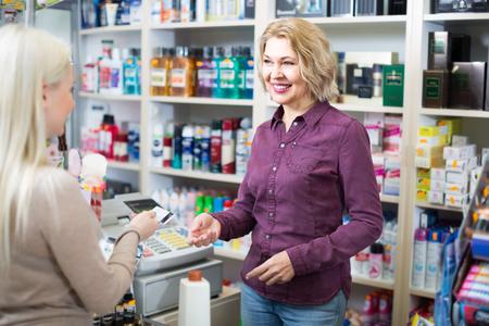 store clerk: Friendly store clerk serving purchaser at cash desk