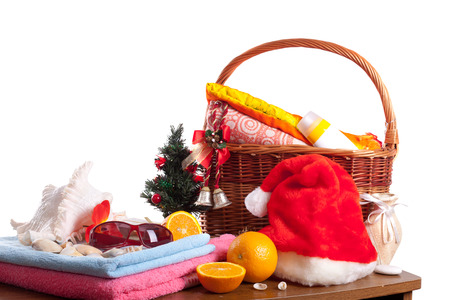 new years vacation: Christmas and beach accessories with basket over white background. New Years  vacation in  tropics