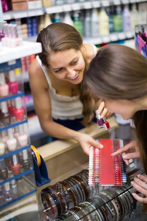 vend: Young girl choosing new nail polish tone at cosmetic shop Stock Photo