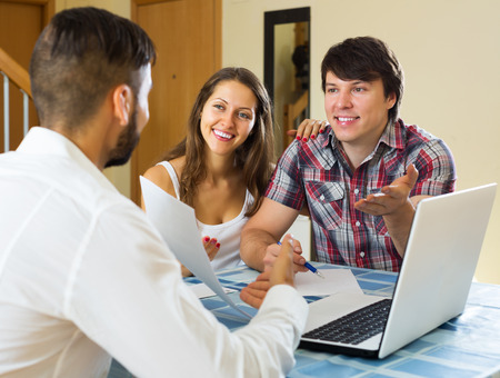 cheerfully: Smiling couple and salesman talking cheerfully about purchase at home