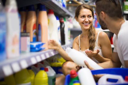 vend: Young american  people choose some detergents in the shop