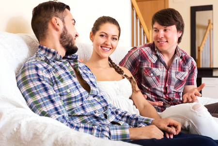 bisexual women: Polyandry: a beautiful woman and two men smiling indoors