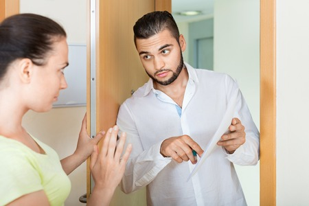 confiscation: Strict businessman trying to collect money from housewife at home door Stock Photo