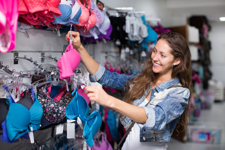 brassiere: Young attractive woman buying brassiere in the clothing store
