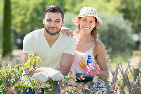 horticultural: Young family in gloves with horticultural sundry in plants garden