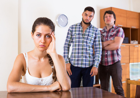 polygamy: Portrait of sad attractive girl and two guys at home: problems of love triangle