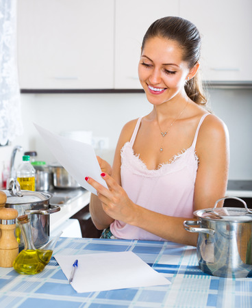 advantaged: Smiling young woman filling documents indoors Stock Photo