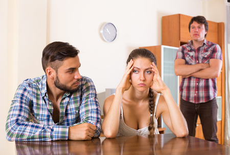 mistrust: Unhappy man having argue with partners at home