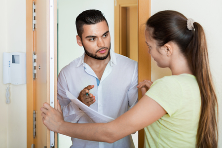confiscation: Young businessman trying to collect money from housewife at  door