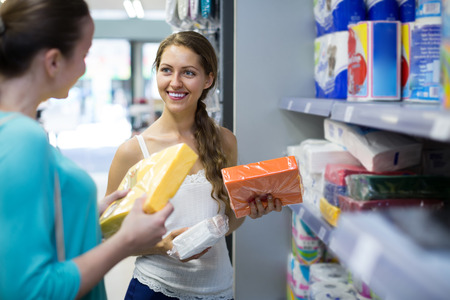 sudarium: Smiling adult girls in good spirits selecting napkins in store Stock Photo