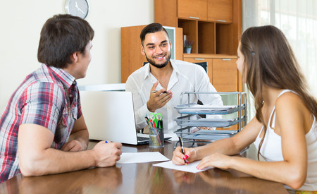 drawing up: Young couple drawing up an agreement with smiling young manager at office Stock Photo