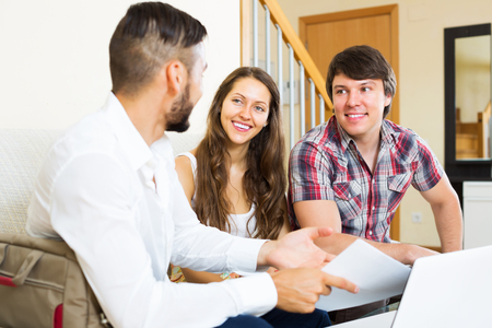 cheerfully: Young couple and salesman talking cheerfully about purchase at home