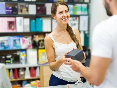 happy client: happy client at shop paying at cash register desk
