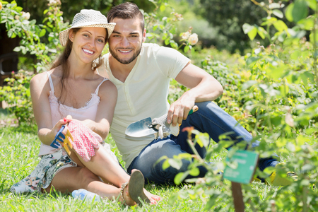 floriculturist: Cheerful married couple at the garden in summer vacation Stock Photo