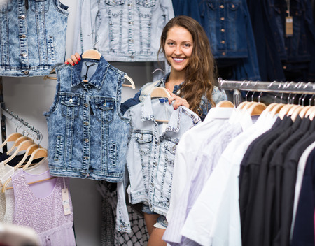 Attractive smiling young girl choosing denim jacket in shop Stock Photo