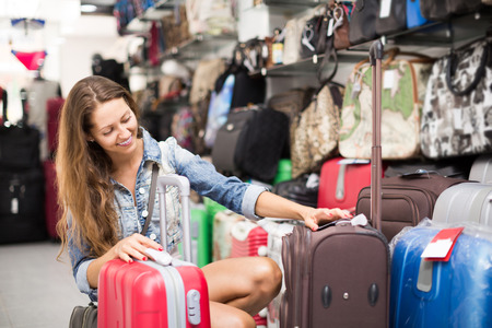 spanish woman: adult spanish woman choosing luggage bag in shop Stock Photo