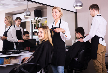 19's: Senior woman cuts hair of blonde girl at the hair salon Stock Photo