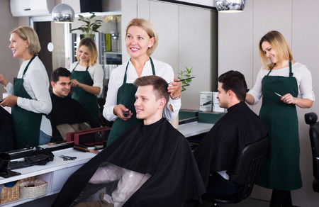 19's: Happy senior woman hairdresser serving teenager guy in chair Stock Photo
