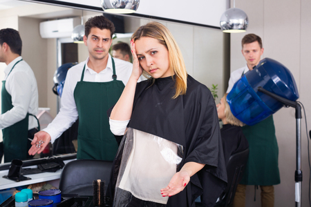 blaming: Young angry woman blaming hairdresser in bad haircut