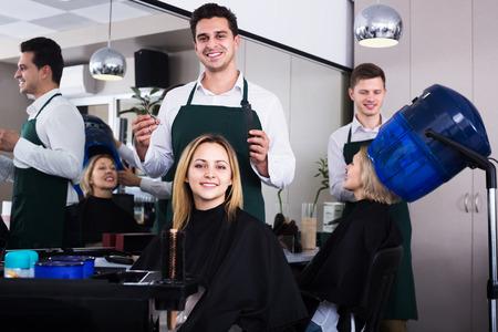 18's: Professional hairdresser cuts hair of blonde girl in barbershop