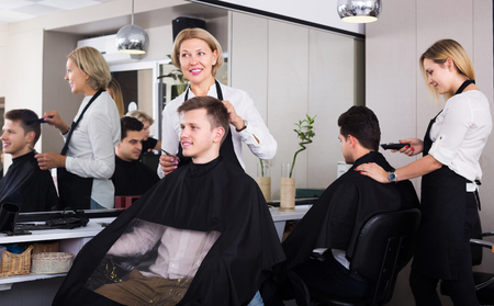 16s: Senior woman hairdresser serving teenager guy in chair Stock Photo