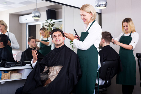16s: Senior female doing hairstyle for adult man in hairdressing saloon