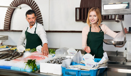 fish selling: Positive cheerful cute shop assistants selling fresh fish and chilled seafood