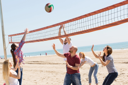 freetime activity: Active cheerful adult friends playing volleyball at sandy beach