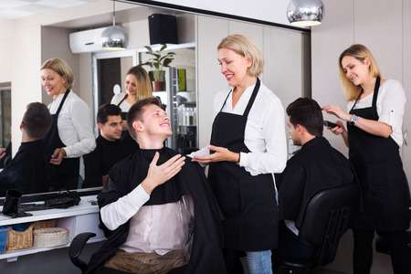 16s: Happy senior female hairdresser serving teenager in chair
